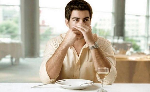 homem-com-cotovelos-na-mesa-e-palitando-o-dente